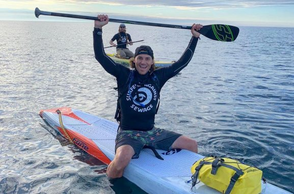 Surfer Alan Stokes on his paddle against plastic